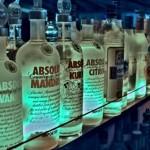 Bouteilles de vodka sur une étagère éclairée en bleu dans un bar